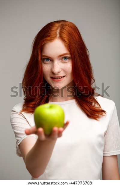 Portrait of beautiful ginger girl holding apple blurred over gray background.