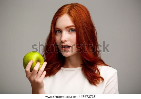 Portrait of beautiful ginger girl holding green apple over gray background.