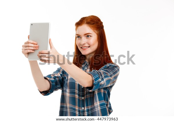 Portrait of beautiful ginger girl making selfie over white background.