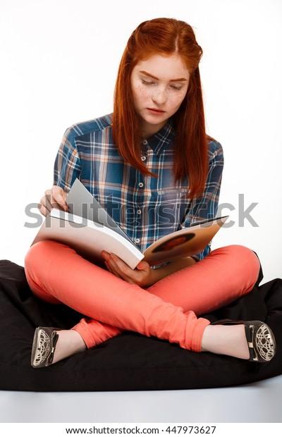 Portrait of beautiful ginger girl reading magazine over white background.