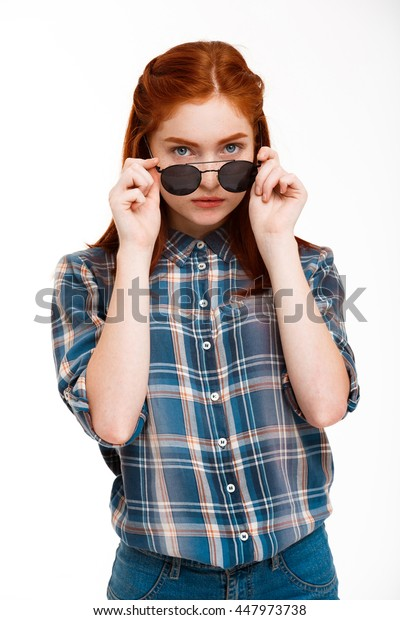 Portrait of beautiful ginger girl in sunglasses over white background.