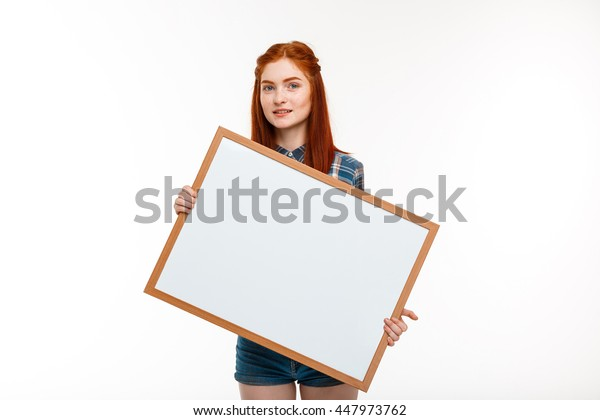 Portrait of beautiful ginger girl with whiteboard over white background.