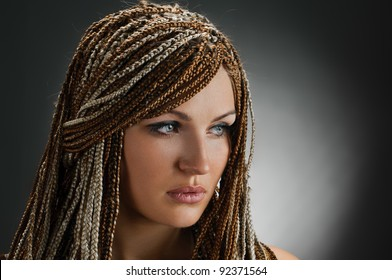portrait of beautiful girl with african plaits on grey