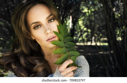 Portrait of beautiful girl with ashberry leaf
