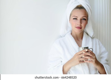 Portrait of beautiful girl in bathrobe with a cup of tea, home style relaxation concept blonde woman wearing bathrobe and towel on head after shower. Spa woman in bathrobe and turban