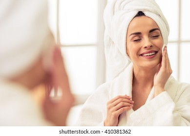 Portrait of beautiful girl in bathrobe and with towel on her head cleaning her face with sponge and smiling, standing with closed eyes