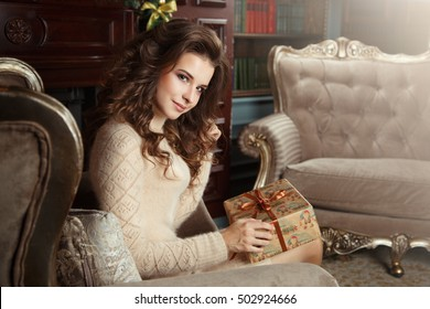 Portrait of a beautiful girl in a beige sweater at Christmas interior.