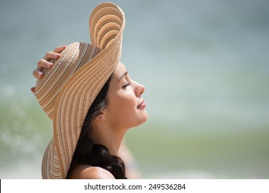 Portrait of a beautiful girl with a big hat at the beach, a loving woman is enjoying the sunlight in her swimsuit