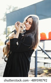 Portrait beautiful girl in a black clothes holding a dog outdoors