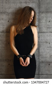 Portrait of beautiful girl in black dress and leather handcuffs