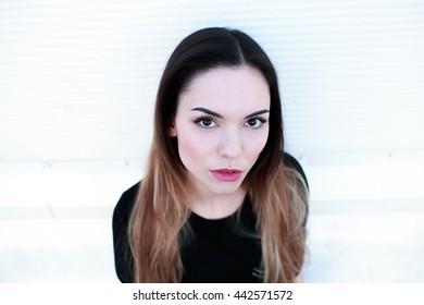 Portrait of beautiful girl in black dress on light background