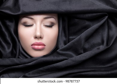 Portrait of beautiful girl in black fabric with closed eyes