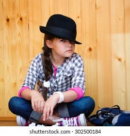 Portrait of a beautiful girl in a black hat