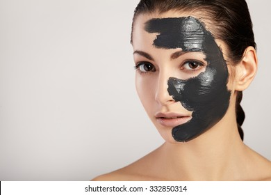 Portrait of a beautiful girl with a black mask of clay on her face.