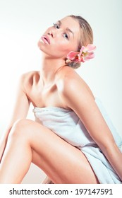 portrait of beautiful girl blonde young woman having spa procedures having fun relaxing sitting in towel and lily flower in her head & looking at camera isolated on white background image