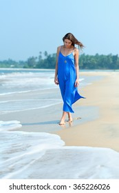 Portrait of a beautiful girl in a blue dress walking along the seashore