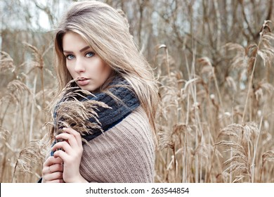 portrait of a beautiful girl with blue eyes in a grey jacket in the field among trees and tall dry grass, tinted in shades of gray
