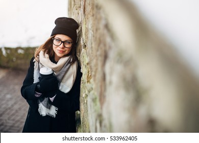 deb3046911 Portrait of a beautiful girl with blue eyes in black glasses in a black hat  and