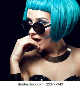 Portrait of beautiful girl with blue hair and yellow glasses, posing in studio