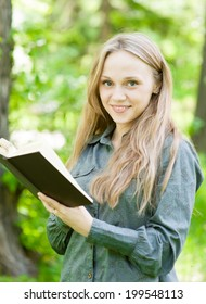 portrait of beautiful girl with book in park