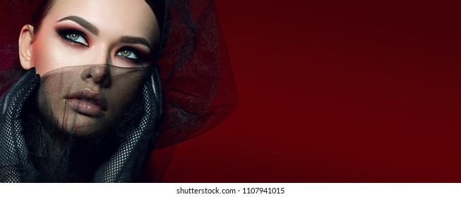 portrait of a beautiful girl with bright green eyes, bright makeup and smooth hair. Gloves in a mesh on their hands, black veil.