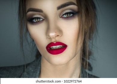 portrait of beautiful girl with brown eyes and red lips looking at the camera in studio