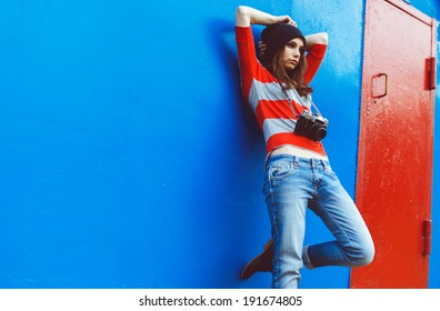 portrait of a beautiful girl with a camera resting on a red wall and blue door