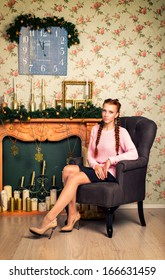 Portrait of a beautiful girl in a chair near the fireplace Christmas