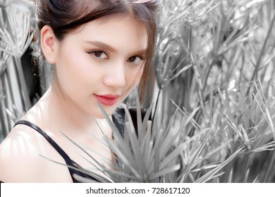 Portrait beautiful girl: Charming girl is looking to someone. Attractive girl looks so confident and happy. She gets little smile on her face. She has beautiful skin and healthy with gray background