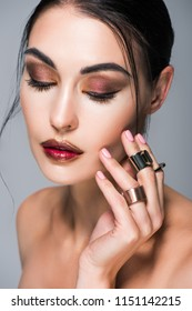 portrait of beautiful girl with closed eyes posing with golden rings on hand, isolated on grey