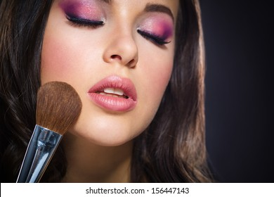 Portrait of beautiful girl with closed eyes applying bright pink make-up on grey background. Concept of beauty and fashion