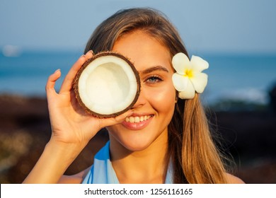 Portrait of beautiful girl close-up snow-white smile,blue eyes and perfectly clean skin holding an open dry coconut near face.female model on the beach happy tropical paradise coco nut oil face care
