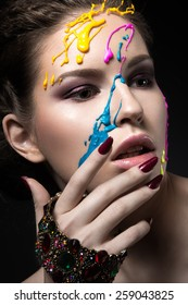 Portrait of a beautiful Girl with color paint on her face. Photo shot in the Studio on a black background.