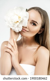 Portrait of a beautiful girl covering half of the face with a flower. Freshness and beauty. Clean skin.