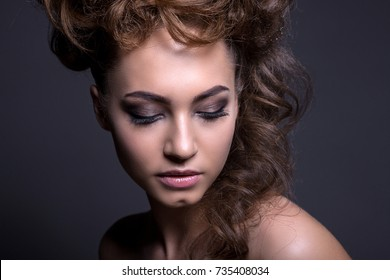 Portrait of a beautiful girl with a creative high hairstyle and makeup. With sequins on the skin and in the hair, on a gray background.