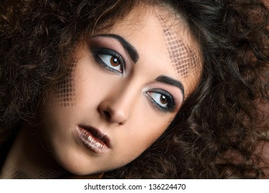 portrait of beautiful girl with curly hair and art make-up