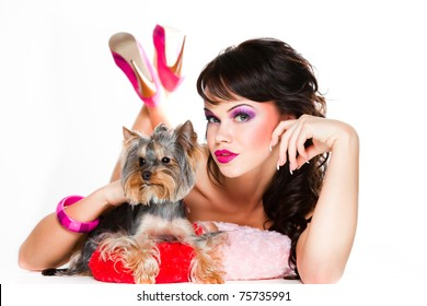 Portrait of beautiful girl with dark long curly hair and vibrant make-up wearing pink satiny ribbon holding small dog on white background
