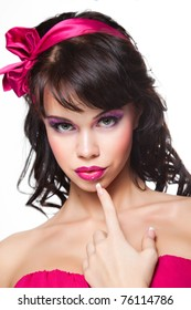 Portrait of beautiful girl with dark long curly hair and vibrant make up wearing pink satiny ribbon on white background