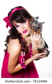 Portrait of beautiful girl with dark long curly hair and vibrant make up wearing pink satiny ribbon holding small small yorkshire terrier on white background