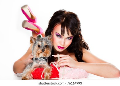 Portrait of beautiful girl with dark long curly hair and vibrant make up wearing pink satiny ribbon holding small yorkshire terrier on white background