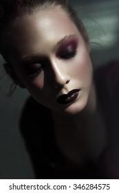 Portrait of a beautiful girl with dark vinous art make up