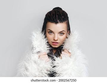 Portrait of a beautiful girl with dreadlocks. Fashionable fur coat. Beauty.