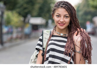 portrait of a beautiful girl with dreadlocks on the street
