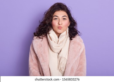 Portrait of beautiful girl dresses winter faux fur coat looking at camera and making kiss gesture isolated over lilac studio background, female wears only eco furs, lady with dark wavy hair. Winter.