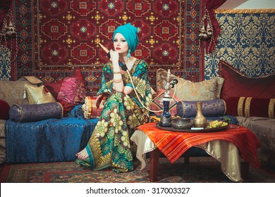 Portrait of a beautiful girl in eastern dress and jewelry. The girl gracefully sitting on cushions among the carpet with a hookah in the hands of