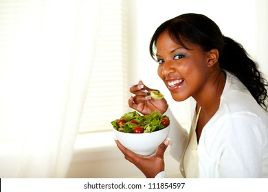 Portrait of a beautiful girl eating vegetable salad and looking at you on light indoor background. With copyspace.