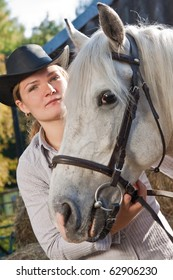 Portrait of a beautiful girl embracing a horse