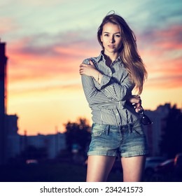 Portrait of Beautiful Girl in Evening City Embracing Herself. Urban Fashion Concept. Copy Space.