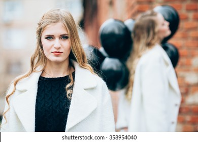 Portrait of beautiful girl in fashionable clothes with black balloons