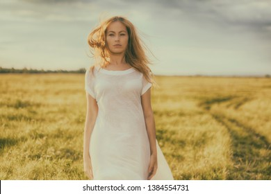 Portrait of beautiful girl in field. Beautiful blond girl on green field with flowers. Rural scene